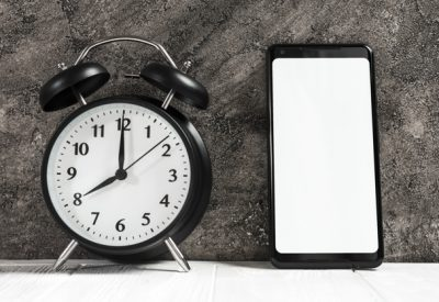 movil junto a despertador para establecer doble alarma